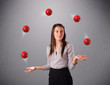 young girl standing and juggling with red balls