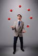 young man standing and juggling with red balls