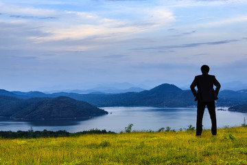 Businessman standing on a green grass in the mountains