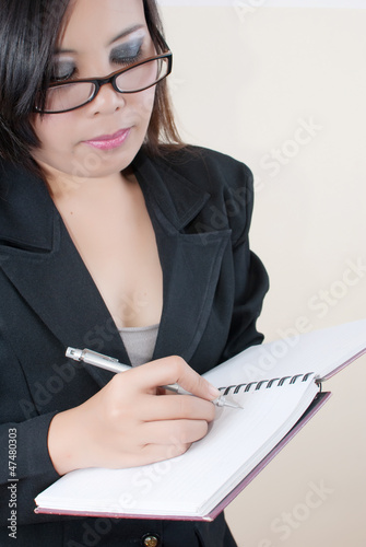 Business lady write on the notebook.