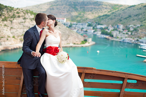 newlyweds posing on the background beautiful mountains and bay