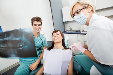 Dentist With Female Assistant Showing X-Ray Image To Patient