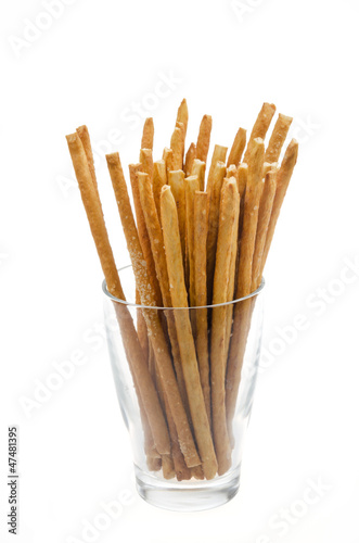 Bread sticks with salt in a glass beaker isolated