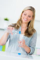 junge frau schenkt ein glas wasser ein