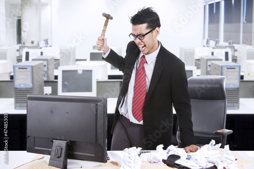 Angry businessman throw hammer at computer