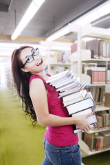 Female student carry books at library