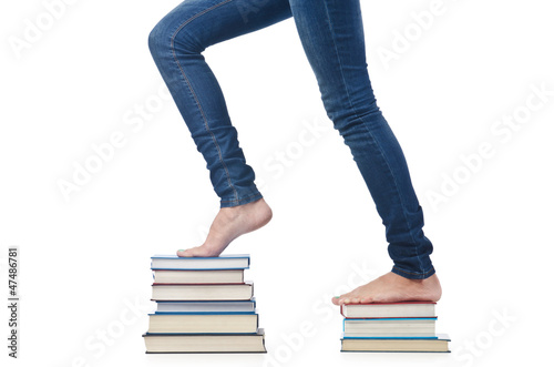 Student sitting on stack of books