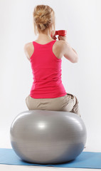 Woman sitting on a ball and doing exercise with dumbbells