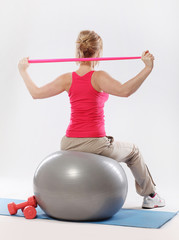 Woman doing exercise with tape view from the back