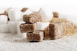 Little heap of white and brown sugar cubes on a wooden surface