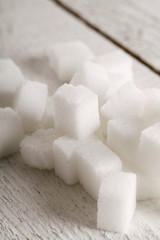 White sweet sugar cubes over wooden surface close up