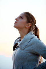 Portrait of slim sporty girl with sky background