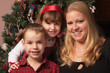 Cute Children and Mother Posing in Front Of Holiday Tree