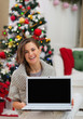 Smiling woman showing laptop blank screen near Christmas tree