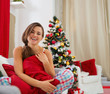 Smiling woman in pajamas sitting on sofa near Christmas tree