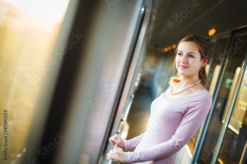 Young woman traveling by train, watching the  country side