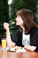 Веселая девушка ест овощной салат