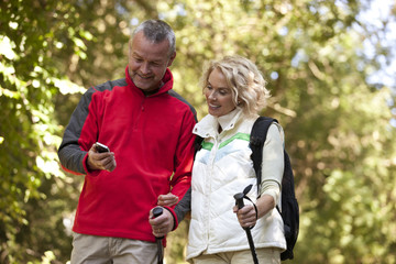 A mature couple walking, looking at a smartphone