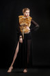 Fashion Woman in Luxury Fur Coat over Black Background posing