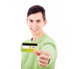 Smiling young casual man holding a credit card on white backgrou
