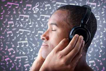 Beautiful African American man listening to music on musical not