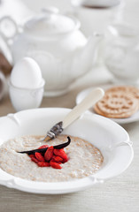 Oat bran porridge with vanilla and goji berries. Selective focus