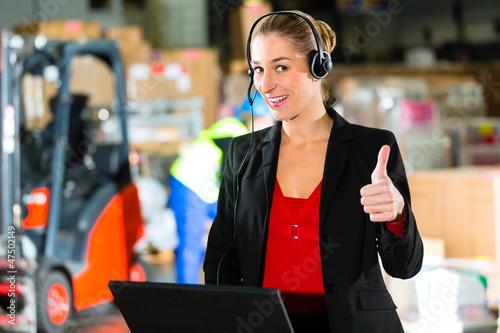 Frau mit Headset in Lagerhalle einer Spedition