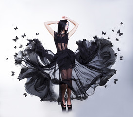 Sensual Woman in Black Fluttering Dress with Butterflies. Swing.