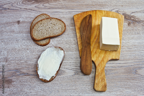 A butter knife and bread on the wooden background