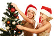 Two girlfriends in santa hat standing near Christmas