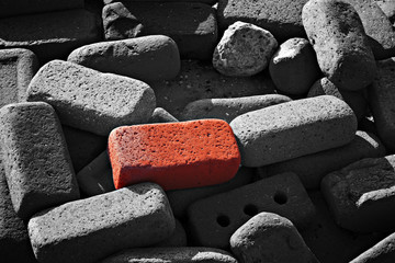 Single red brick amongst lots of monochrome bricks