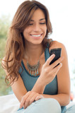 Woman Smiling And Holding Mobile Phone
