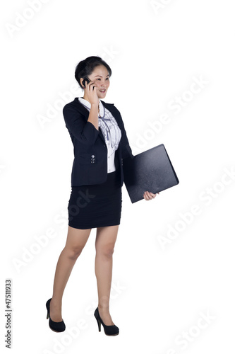 Full length of businesswoman walking talking on mobile phone and