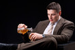 Young businessman sitting on a couch with an alcoholic beverage