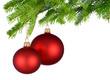 Zwei rote Christbaumkugeln hängen am Tannenzweig