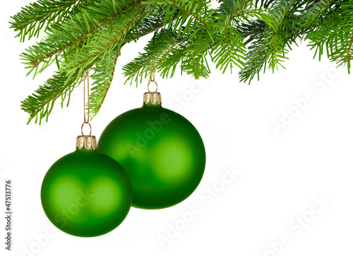Zwei grüne Christbaumkugeln hängen am Tannenzweig