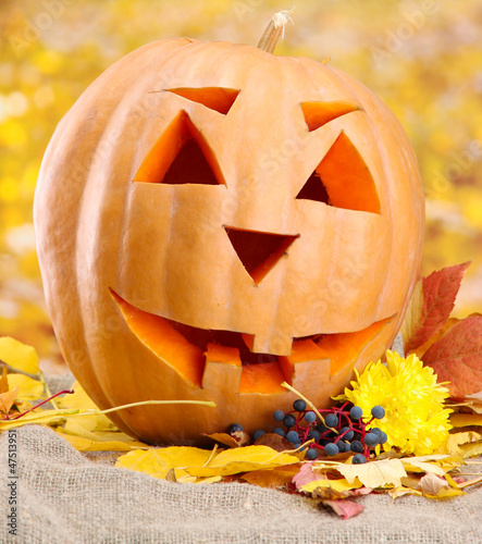 halloween pumpkin and autumn leaves, on yellow background