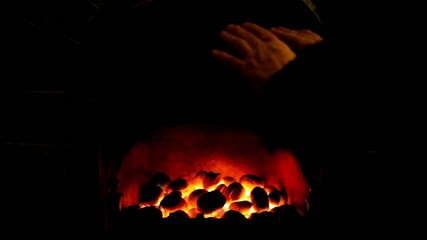 hands warmed by a coal fire