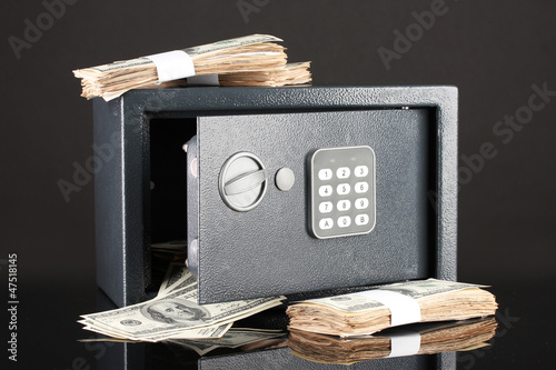 Money in open safe isolated on black
