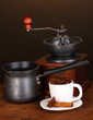 Coffee maker with coffe mill and white cup on wooden table