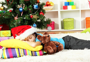 Little girl sleeping near christmas tree