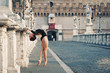 Young beautiful ballerina dancing on Castel Santangelo bridge.