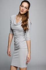Elegant woman in gray dress posing in studio