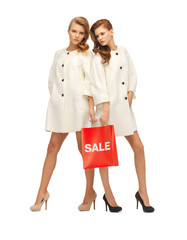 teenage girls in white coats with shopping bags