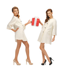 two teenage girls in white coats with present box