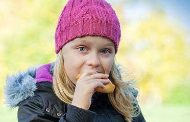 little beautiful blond girl eating cake in autumnal park