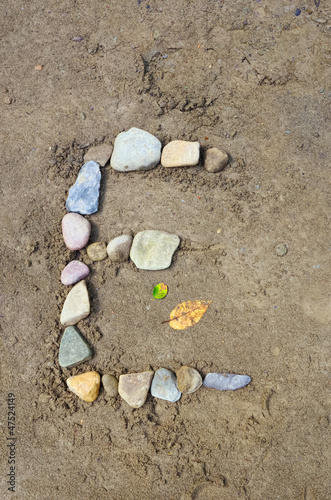 The Letter E with Stones on Sand