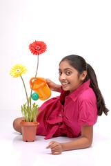 Beautiful young girl watering a plant