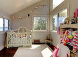 Baby girl room with white crib and clothes.
