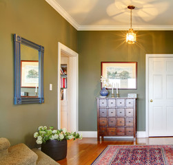 Classic Hallway with green walls, flowers and rug.